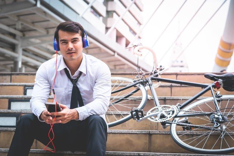Χαλάρωση επιχειρησιακών ατόμων που ακούει τη μουσική με το ποδήλατό του επάνω στοκ εικόνες με δικαίωμα ελεύθερης χρήσης