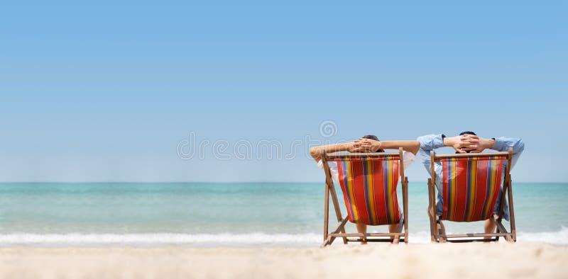 Χαλάρωση ζεύγους στην παραλία καρεκλών πέρα από το υπόβαθρο θάλασσας στοκ εικόνα με δικαίωμα ελεύθερης χρήσης