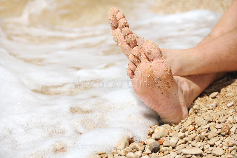 Χαλάρωση στην παραλία, λεπτομέρεια των αρσενικών ποδιών στοκ εικόνες