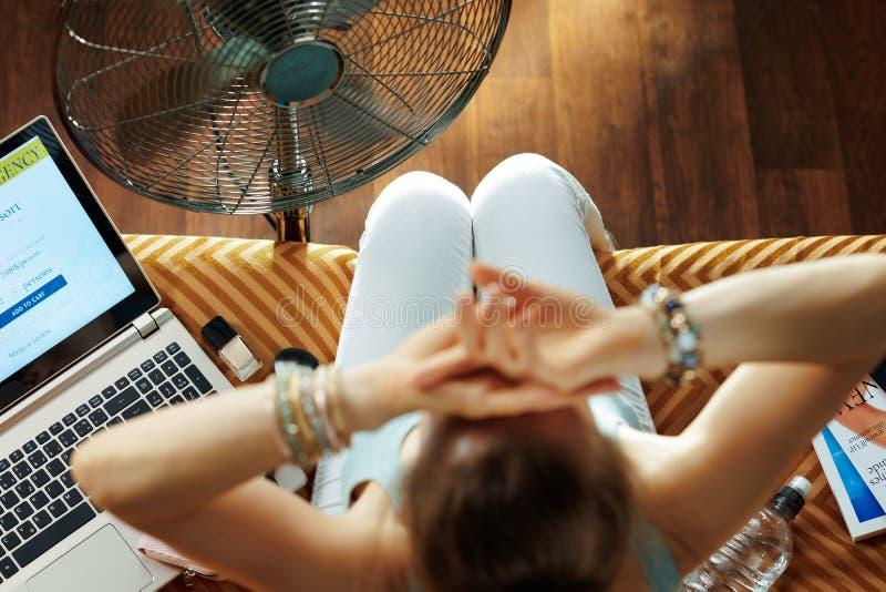 Χαλαρή νεαρή γυναίκα που χρησιμοποιεί ηλεκτρικό ανεμιστήρα στο πάτωμα στοκ φωτογραφία με δικαίωμα ελεύθερης χρήσης