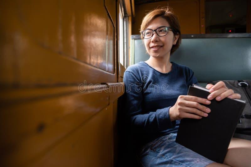 Χαλαρωμένα ασιατικά γυαλιά ένδυσης τουριστών γυναικών που κρατούν το βιβλίο μέσα στο tra στοκ φωτογραφίες