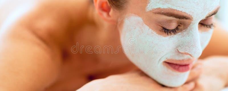 Χαλαρωμένη γυναίκα με την αναζωογοηση της μάσκας στο πρόσωπο που βάζει στο MAS στοκ φωτογραφία