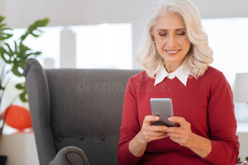 Χαλαρωμένη γυναίκα που κοιτάζει βιαστικά Διαδίκτυο στο smartphone της στοκ φωτογραφία με δικαίωμα ελεύθερης χρήσης