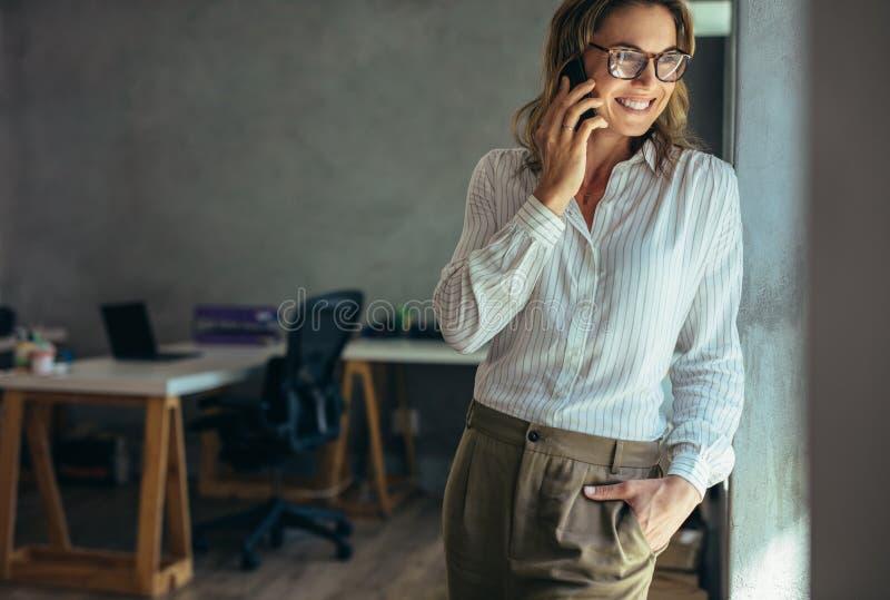 Χαλαρωμένη επιχειρηματίας που μιλά στο τηλέφωνο κυττάρων στοκ εικόνες
