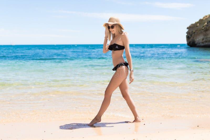 Χαλαρωμένη νέα γυναίκα που περπατά στο μπικίνι που απολαμβάνει τις τροπικές θερινές διακοπές παραλιών στοκ φωτογραφία