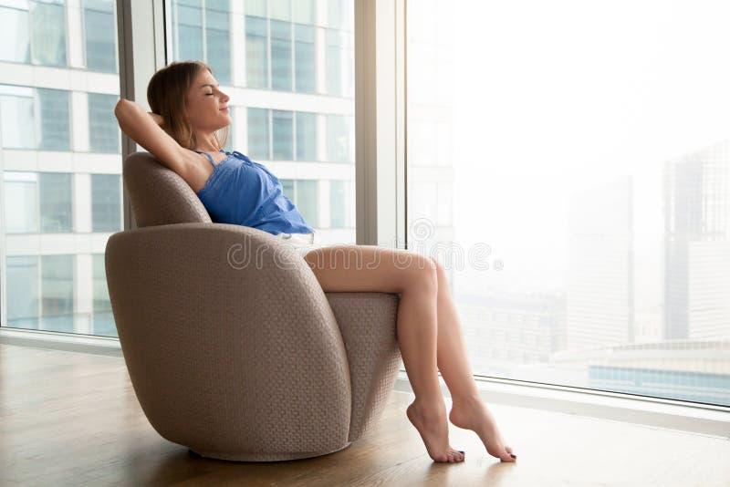 Χαλαρωμένη νέα γυναίκα που στηρίζεται στην άνετη σύγχρονη πολυθρόνα στο ho στοκ εικόνες