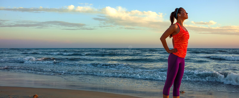 Χαλαρωμένη νέα γυναίκα στο αθλητικό εργαλείο seacoast στο ηλιοβασίλεμα στοκ φωτογραφίες με δικαίωμα ελεύθερης χρήσης