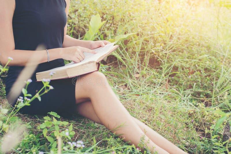 Χαλαρωμένη νέα όμορφη γυναίκα που διαβάζει ένα βιβλίο στο χορτοτάπητα με το SU στοκ φωτογραφία με δικαίωμα ελεύθερης χρήσης