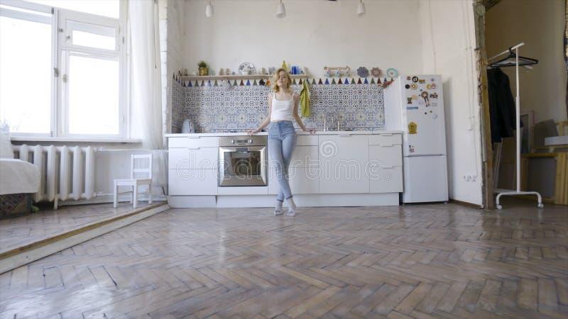 Χαλαρωμένη προκλητική ξανθή τοποθέτηση στην κουζίνα το πρωί r Προκλητική νέα ξανθή γυναίκα στην κουζίνα στο σπίτι στοκ φωτογραφίες