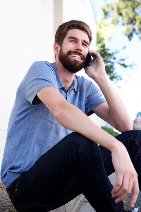 Χαλαρωμένη συνεδρίαση νεαρών άνδρων εξωτερική και που μιλά στο τηλέφωνο στοκ εικόνες