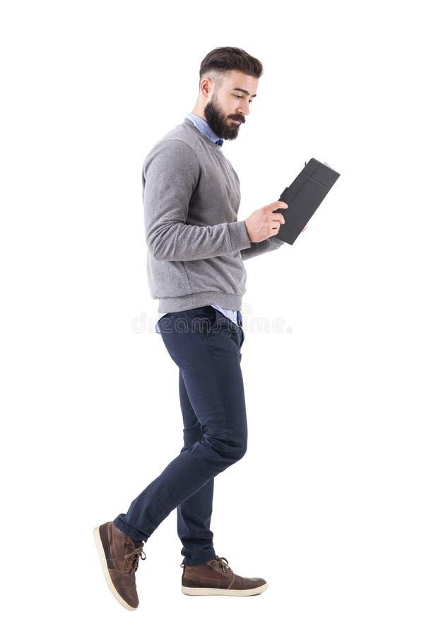 Χαλαρωμένος έξυπνος περιστασιακός επιχειρηματίας που περπατά και που διαβάζει το σημειωματάριο στοκ εικόνες