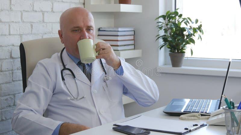 Χαλαρωμένος γιατρός στο δωμάτιο γραφείων που πίνει έναν καφέ στοκ εικόνες με δικαίωμα ελεύθερης χρήσης