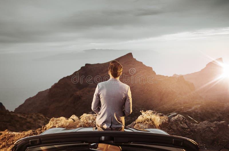 Χαλαρωμένος επιχειρηματίας που στηρίζεται και που προσέχει το ηλιοβασίλεμα στοκ εικόνες