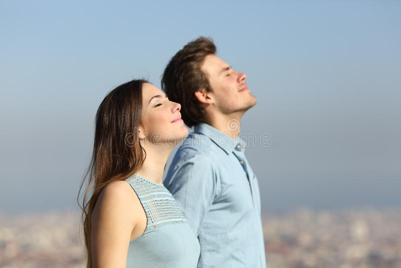 Χαλαρωμένος καθαρός αέρας αναπνοής ζευγών με το αστικό υπόβαθρο στοκ εικόνες με δικαίωμα ελεύθερης χρήσης