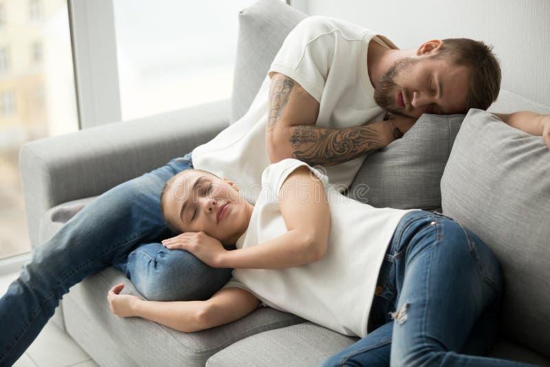 Χαλαρωμένος κουρασμένος ύπνος ζευγών που έχει το NAP στον άνετο καναπέ tog στοκ φωτογραφία με δικαίωμα ελεύθερης χρήσης