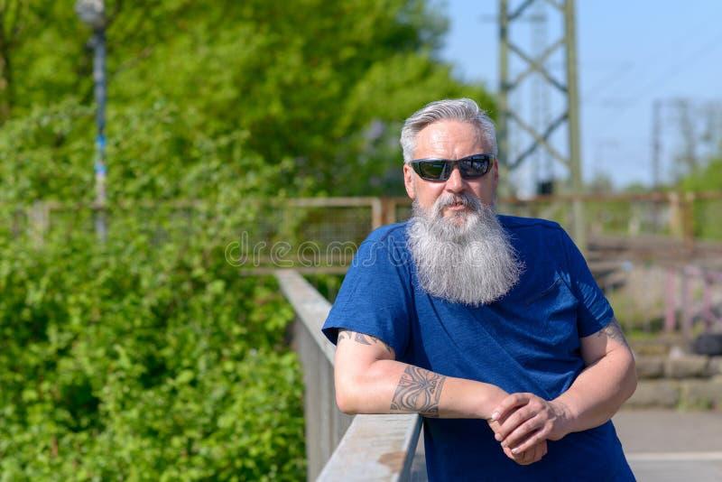 Χαλαρωμένο γενειοφόρο άτομο που στέκεται σε μια γέφυρα στοκ φωτογραφία