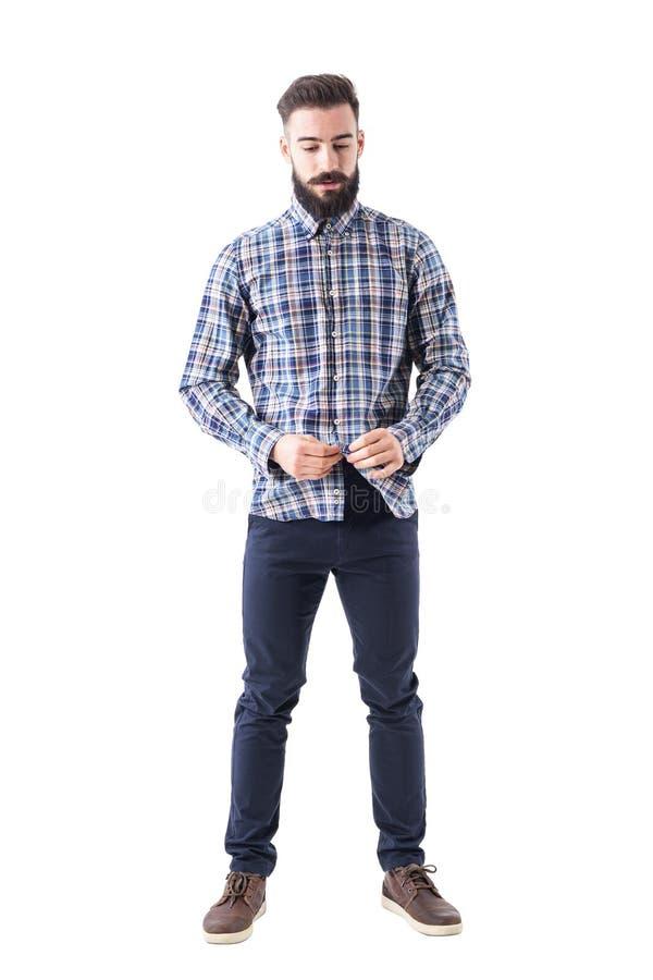 Χαλαρωμένο δροσερό γενειοφόρο hipster που κουμπώνει το ελεγμένο πουκάμισο καρό που κοιτάζει κάτω στοκ εικόνα
