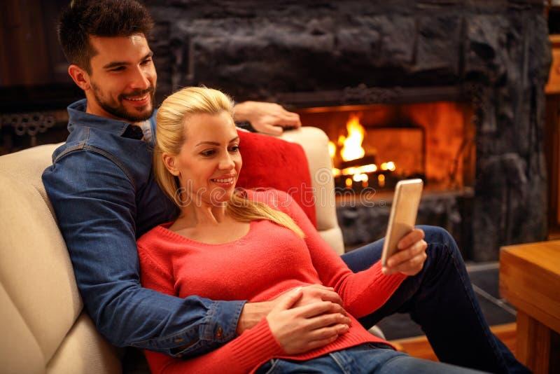 Χαλαρωμένο ζεύγος που χρησιμοποιεί το κινητό τηλέφωνο μαζί στον καναπέ στοκ φωτογραφίες
