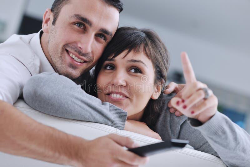 Χαλαρωμένο νέο ζεύγος που προσέχει τη TV στο σπίτι στοκ εικόνα με δικαίωμα ελεύθερης χρήσης