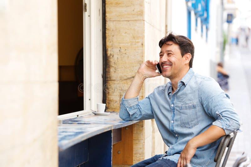 Χαλαρωμένο ώριμο άτομο στη καφετερία και ομιλία στο κινητό τηλέφωνο στοκ εικόνα