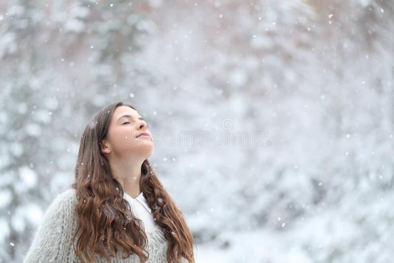 Χαλαρό κορίτσι αναπνέει καθαρό αέρα απολαμβάνοντας χιόνι το χειμώνα στοκ εικόνες