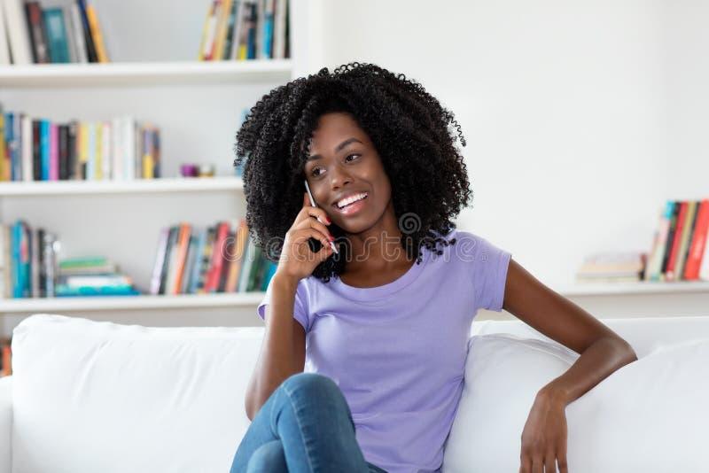 Χαλαρώνοντας γυναίκα αφροαμερικάνων που γελά στο τηλέφωνο στοκ εικόνα
