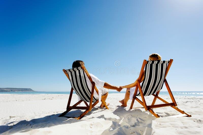 χαλαρώνοντας καλοκαίρι ζευγών παραλιών στοκ φωτογραφία με δικαίωμα ελεύθερης χρήσης