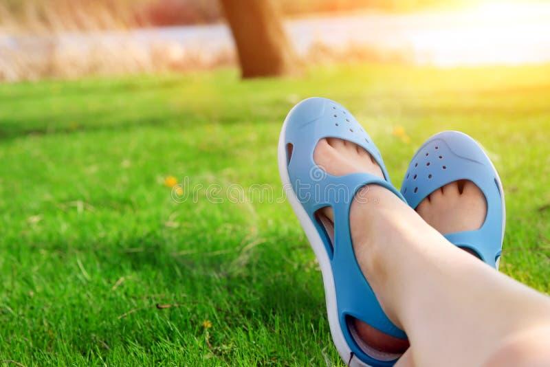 Χαλαρώνοντας νέα γυναίκα σε ένα λιβάδι στο θερινό ήλιο στοκ εικόνα