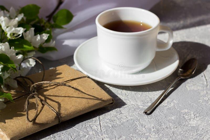 Χαλαρώνοντας χρόνος και ευτυχία με το φλυτζάνι του τσαγιού με μεταξύ του φρέσκου λουλουδιού άνοιξη στοκ εικόνα με δικαίωμα ελεύθερης χρήσης