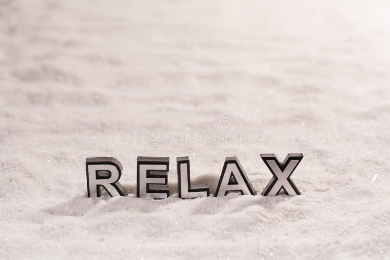 Χαλαρώστε τη λέξη στην άσπρη άμμο στοκ φωτογραφία