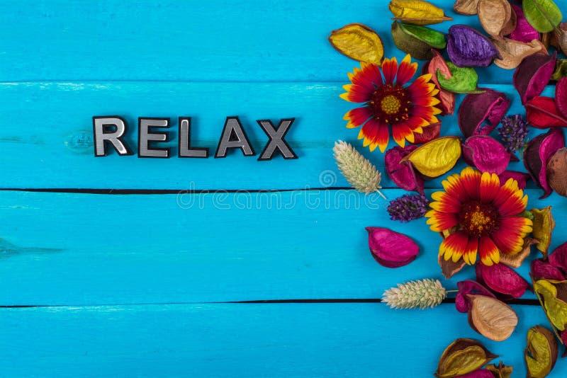 Χαλαρώστε τη λέξη στο μπλε ξύλο με το λουλούδι στοκ εικόνα με δικαίωμα ελεύθερης χρήσης