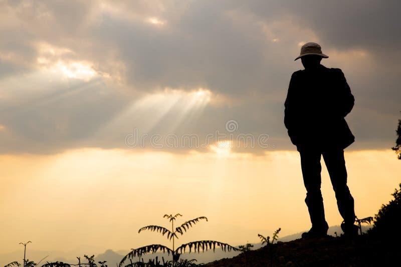Χαλαρώστε το άτομο στο λόφο στο ηλιοβασίλεμα στοκ εικόνες