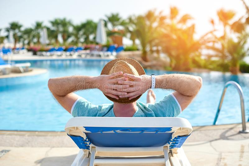 Χαλαρώστε το καλοκαίρι λιμνών Νέο και επιτυχές άτομο που βρίσκεται σε έναν αργόσχολο ήλιων στο ξενοδοχείο στο υπόβαθρο του ηλιοβα στοκ εικόνα με δικαίωμα ελεύθερης χρήσης