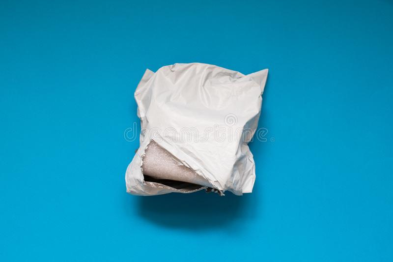 Χαλασμένος φάκελος πολυαιθυλενίου στο μπλε υπόβαθρο Πλαστικές ταχυδρομικές τσάντες αποστολής στοκ φωτογραφία