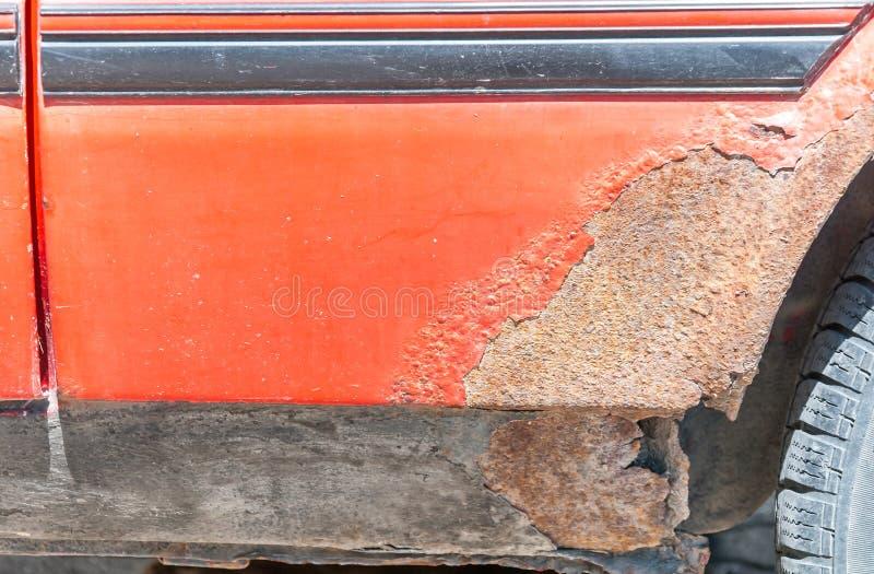 Χαλασμένο κόκκινο σώμα μετάλλων αυτοκινήτων και γρατσουνισμένο χρώμα με τα σκουριασμένα διαβρωμένα μέρη και τρύπα στο κατώτατο ση στοκ εικόνα