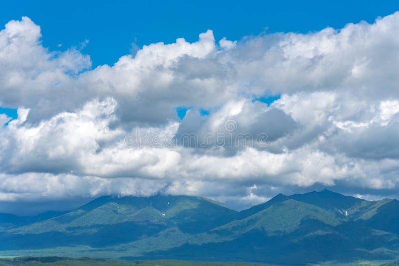 Χαμηλά σύννεφα πέρα από την πράσινους χλόη και το μπλε ουρανό θερινών βουνών στοκ εικόνες