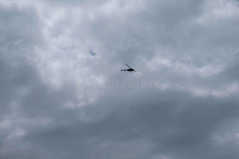 Χαμηλή άποψη γωνίας ενός πετώντας ελικοπτέρου με το νεφελώδη ουρανό ως υπόβαθρο στοκ εικόνα