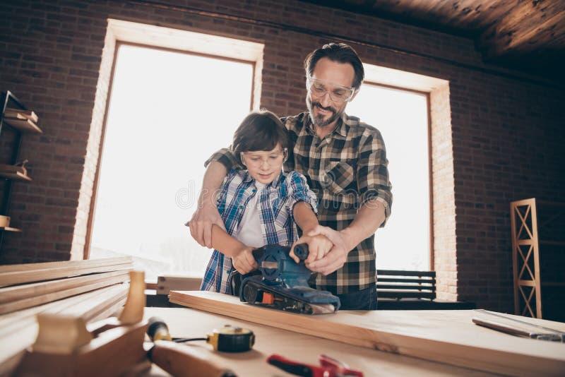 Χαμηλή άποψη γωνίας της συμπαθητικής δημιουργικής εύθυμης εργατικής καθορίζοντας δημιουργίας μπαμπάδων προσώπων δύο κύριας επισκε στοκ φωτογραφία