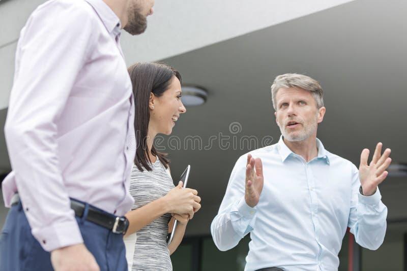 Χαμηλή άποψη γωνίας του διευθυντή που εξηγεί στους συναδέλφους στο πεζούλι γραφείων στοκ εικόνα με δικαίωμα ελεύθερης χρήσης