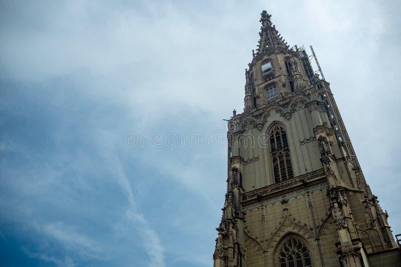 Χαμηλή άποψη γωνίας του πύργου της Βέρνης Munster στο νεφελώδες υπόβαθρο μπλε ουρανού στοκ εικόνες
