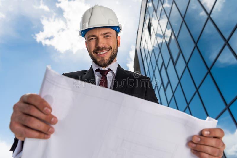 Χαμηλή άποψη γωνίας του χαμόγελου του γενειοφόρου σχεδιαγράμματος εκμετάλλευσης αρχιτεκτόνων και του κοιτάγματος στοκ εικόνα με δικαίωμα ελεύθερης χρήσης