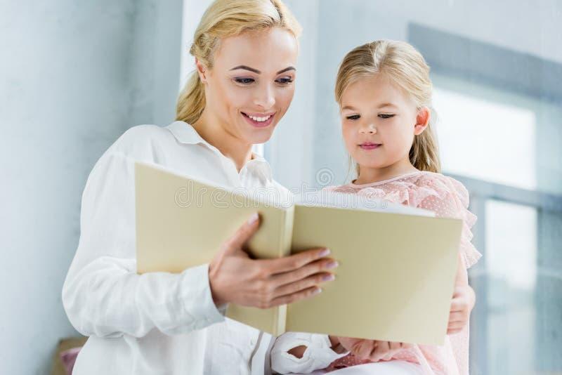 χαμηλή άποψη γωνίας του όμορφου ευτυχούς βιβλίου ανάγνωσης μητέρων και κορών από κοινού στοκ εικόνα με δικαίωμα ελεύθερης χρήσης