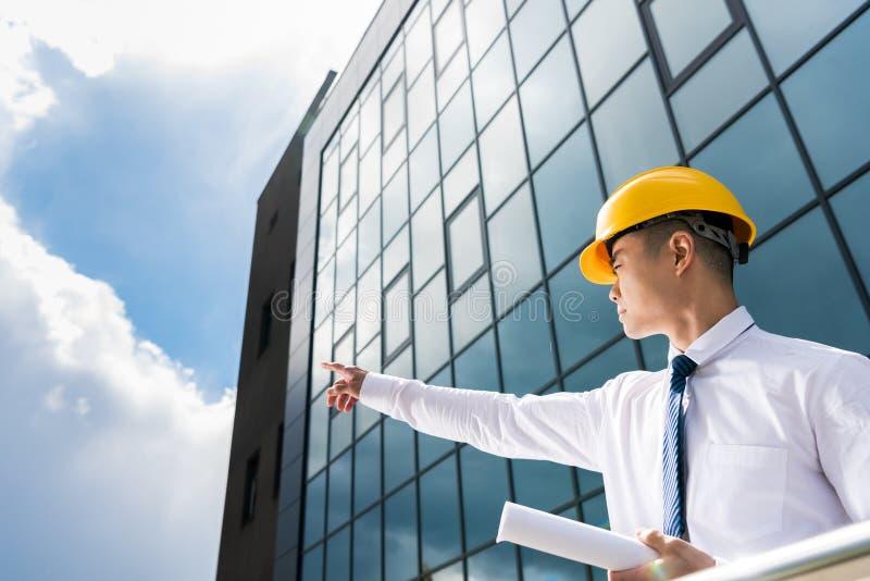 χαμηλή άποψη γωνίας των επαγγελματικών αρχιτεκτόνων στα σκληρά καπέλα που συζητούν τους επιτυχείς επιχειρηματίες προγράμματος στοκ εικόνες