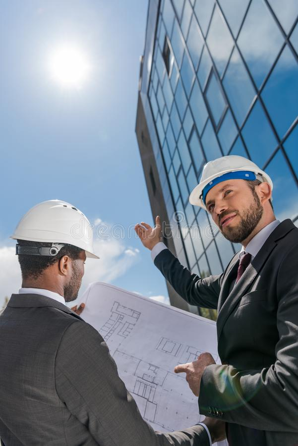 Χαμηλή άποψη γωνίας των επαγγελματικών αρχιτεκτόνων hardhats στην εργασία στοκ εικόνες με δικαίωμα ελεύθερης χρήσης