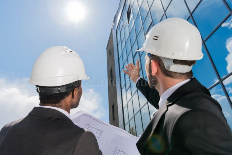 Χαμηλή άποψη γωνίας των επαγγελματικών αρχιτεκτόνων hardhats στην εργασία στοκ φωτογραφία