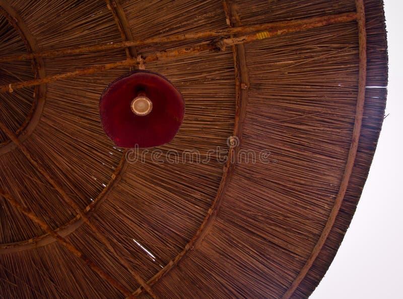 Χαμηλή άποψη γωνίας parasol με τον κόκκινο λαμπτήρα στο ψάθινο σχέδιο αχύρου των γραμμών και του φωτεινού ουρανού στοκ φωτογραφίες