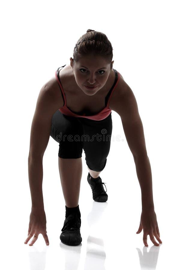 Χαμηλή έναρξη, αθλήτρια που πηγαίνει να τρέξει, να σκιαγραφήσει το στούντιο πυροβοληθε'ν στοκ εικόνες