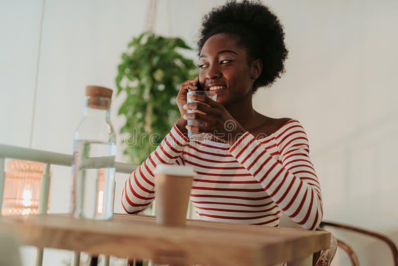 Χαμηλή γωνία της αρκετά αφρικανικής γυναίκας που έχει το υπόλοιπο στον καφέ στοκ εικόνες