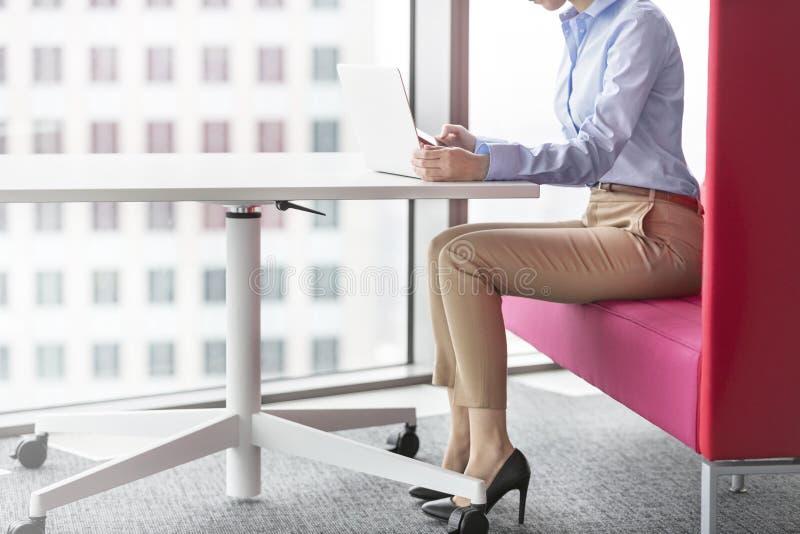 Χαμηλό τμήμα της επιχειρηματία που χρησιμοποιεί το lap-top καθμένος στο γραφείο στοκ φωτογραφία