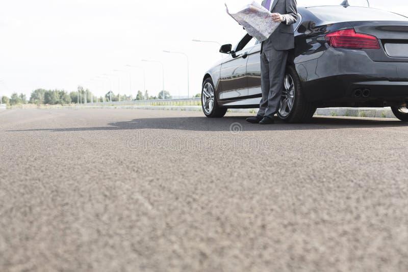 Χαμηλό τμήμα του επιχειρηματία με το χάρτη στεμένος έξω από το αυτοκίνητο στο δρόμο στοκ εικόνες